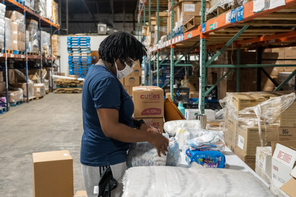 Member of The Junior League of Tampa packing diapers